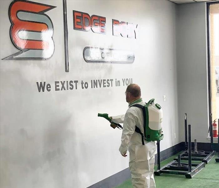 man in personal protective equipment spraying a gym with a disinfectant